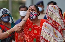 A woman mourns after her husband died due to the coronavirus disease (COVID-19) outside a mortuary of a COVID-19 hospital in Ahmedabad, India, May 8, 2021.