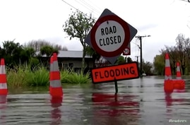 """Video grab of a sign reading """"Road Closed. Flooding"""" in floodwaters in Canterbury region, New Zealand"""