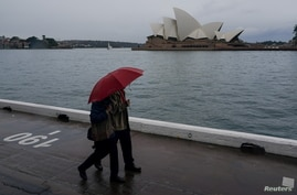 People share an umbrella while walking near the Opera House in Sydney