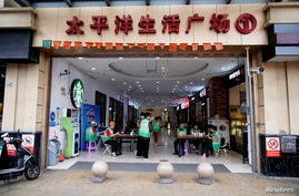 Staff members sit at the entrance of a mall to check for COVID-19 vaccination credentials in Shanghai