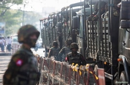 FILE PHOTO: Soldiers stand next to military vehicles as people gather to protest against the military coup, in Yangon