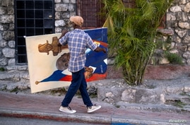 A man carries a painting of President Jovenel Moise in the Petion-Ville neighborhood in Port-au-Prince