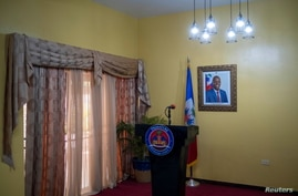 A picture of the late Haitian President Jovenel Moise hangs on a wall before a news conference