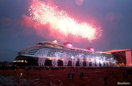 FILE PHOTO: People watch 'float out' of newly built cruise ship Disney Dream at the Meyer shipyard in Papenburg