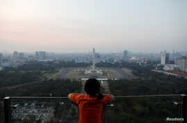 A girl looks on National Monument (Monas) as smog covers the capital city of Jakarta, Indonesia, July 4, 2019.