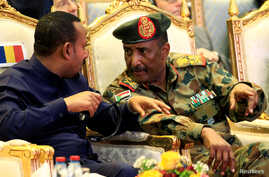 Sudan's Head of Transitional Military Council, Lieutenant General Abdel Fattah Al-Burhan, talks to Ethiopia's Prime Minister Abiy Ahmed during the signing of the power sharing deal, that paves the way for a transitional government, and eventual elections, following the overthrow of long-time leader Omar al-Bashir, in Khartoum, Sudan, August 17, 2019. REUTERS/Mohamed Nureldin Abdallah