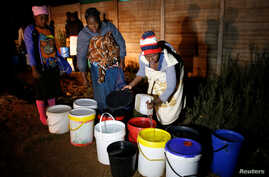 Residents collect water at night from an electric-powered well, as the country faces 18-hour daily power cuts, in a suburb of Harare, Zimbabwe, July 30, 2019.