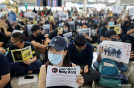 Anti-extradition bill protesters hold up placards for arriving travelers during a protest at the Hong Kong International Airport in Hong Kong, Aug. 9, 2019.