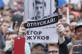 A supporter of student and blogger Yegor Zhukov, who was detained during a recent protest for fair elections, holds a placard during a rally to demand authorities allow opposition candidates to run in the upcoming local election in Moscow, Russia August 10, 2019. REUTERS/Maxim Shemetov