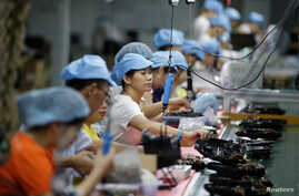 Employees work on the production line of a robot vacuum cleaner  factory of Matsutek in Shenzhen, China August 9, 2019. Picture taken August 9, 2019. REUTERS/Jason Lee