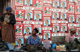 Women, selling charcoal, chat in front of the ruling FRELIMO party election posters in the capital, Maputo, Mozambique August…