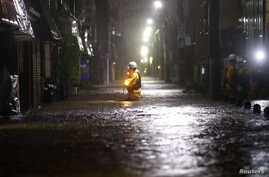 Firefighters patrol on a flooded road due to heavy rains caused by Typhoon Hagibis at Ota ward in Tokyo, Japan, October 12,…