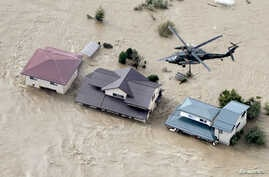 An aerial view shows a Japan Self-Defence Force helicopter flying over residential areas flooded by the Chikuma river following…