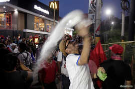 A demonstrator throws a plastic bag with white powder during a protest against the government of president Juan Orlando…