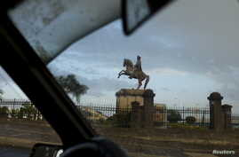 A statue of King Menelik II, the founder of Addis Ababa, is seen through the front windscreen of a taxi, in the capital Addis…