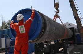FILE PHOTO: A worker puts a cap to a pipe at theconstruction siteof the NordStream2 gas pipeline, near the town of…