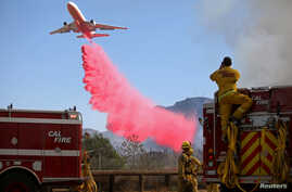 Cal Fire firefighters look on as a plane drops fire retardant on the Maria Fire in Santa Paula, California, U.S. November 1,…