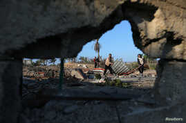 Palestinians inspect a site belonging to Hamas after it was targeted by Israeli warplanes in the southern Gaza Strip November 2…