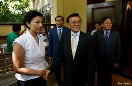 Leader of the Cambodia National Rescue Party (CNRP) Kem Sokha shakes hands with French Ambassador to Cambodia Eva Nguyen Binhin…