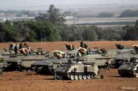 Israeli soldiers stand atop armored personnel carriers