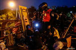 Anti-government protesters scout at a makeshift gate during a standoff with riot police at the Chinese University of Hong Kong,…