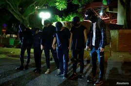 Anti-government protesters wait to give themselves up to the police as they leave the campus of the Polytechnic University …