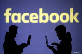FILE PHOTO: Silhouettes of laptop users are seen next to a screen projection of Facebook logo in this picture illustration…