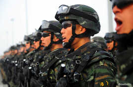 Paramilitary policemen stand in formation as they take part in an anti-terrorism oath-taking rally, in Kashgar, Xinjiang Uighur…