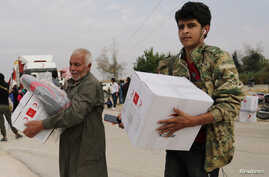 People hold boxes of aid donated by the Turkish Red Crescent in the border town of Tal Abyad, Syria October 19, 2019. REUTERS…