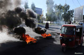 A tuk-tuk drives past burning tires during ongoing anti-government protests in Kerbala, Iraq  December 23, 2019. REUTERS…