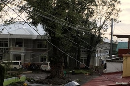 Fallen power lines dangle over buildings after Typhoon Phanfone swept through Tanauan, Leyte, in the Philippines December 25,…
