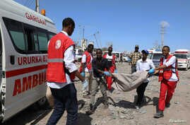 SENSITIVE MATERIAL. THIS IMAGE MAY OFFEND OR DISTURB  Civilians carry the dead body of a man killed in a car bomb explosion at…