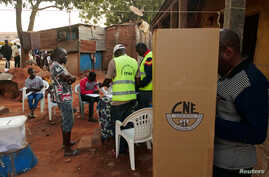 A man prepares to cast his ballot at a polling station during the second round of Guinea Bissau's presidential election in…