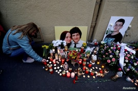 FILE PHOTO: A woman kneels by a memorial on the first anniversary of the murder of the investigative reporter Jan Kuciak and…