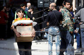 A boy holds a cardboard box of food aid received from World Food Programme in Aleppo's Kalasa district, Syria April 10, 2019…