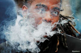 A demonstrator vapes during a protest at the Massachusetts State House against the state's four-month ban of all vaping product…