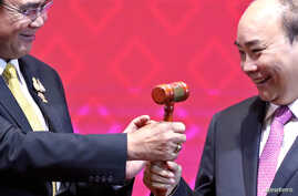 Vietnam's Prime Minister Nguyen Xuan Phuc takes the gavel from Thai Prime Minister Prayuth Chan-Ocha who hands over the ASEAN…