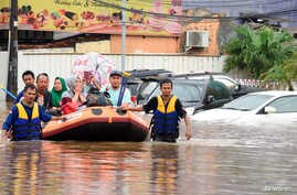A rescue team evacuates locals on an inflatable boat during a flood after heavy rain in Bekasi, near Jakarta, Indonesia January…