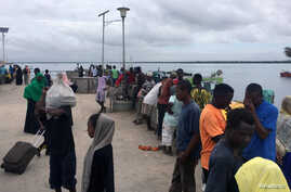 Travellers are seen gathered at the Lamu jetty following an attack by Somalia's Islamist group al Shabaab on a military base in…