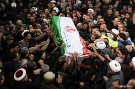 Iranian people carry a coffin of Iranian Major-General Qassem Soleimani, head of the elite Quds Force, who was killed in an air…