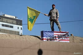 An Iranian guard holds a Hezbollah flag during a funeral procession and burial for Iranian Major-General Qassem Soleimani, head…