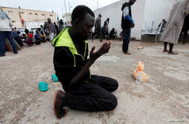 FILE PHOTO: An illegal African migrant prays at a detention camp in Tripoli, Libya, March 22, 2017. REUTERS/Ismail Zitouny -…
