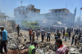 Smoke rises while people gather at a damaged site after two bomb blasts claimed by Islamic State hit the northeastern Syrian…