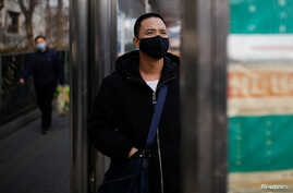 A man wearing a face mask looks at a board at a bus stop, as the country is hit by an outbreak of the new coronavirus, in…