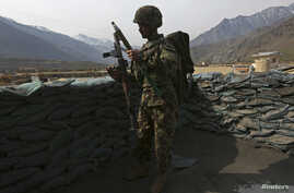 An Afghan National Army (ANA) soldier keeps watch at the Forward Base in Nari district near the army outpost in Kunar province,…