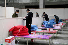 Workers set up infrastructure at the Wuhan International Conference and Exhibition Center to convert it into a makeshift…