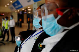 FILE PHOTO: Health workers waits to screen travellers for signs of the coronavirus at the Kotoka International Airport in Accra…
