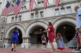 FILE PHOTO: A group of people approach the front facade of the Trump International Hotel to pose for photos in Washington, U.S…