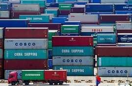 FILE PHOTO: A truck carrying containers are seen near a Chinese flag at the Yangshan Deep Water Port in Shanghai, China August…