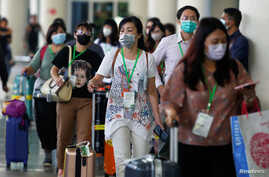 Passengers wearing medical masks walk as they arrive at international arrival terminal of I Gusti Ngurah Rai airport following…